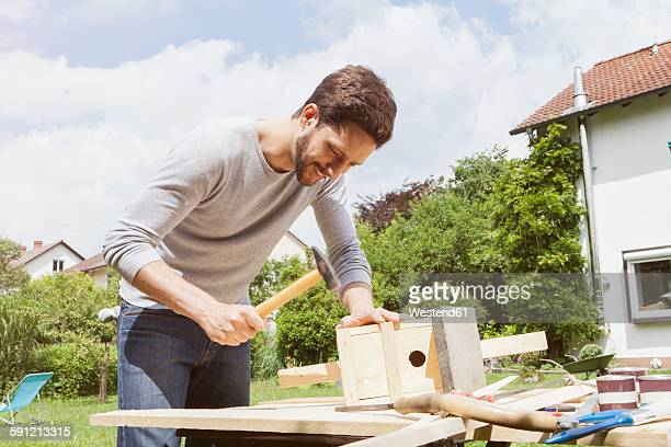 man timbering a birdhouse - birdhouse stock pictures, royalty-free photos & images
