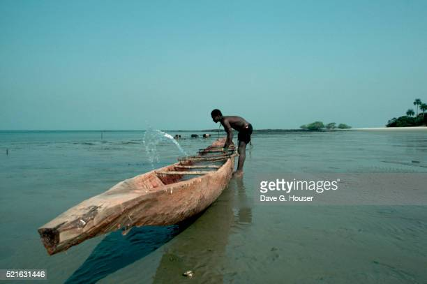 Man Tipping Boat on Beach