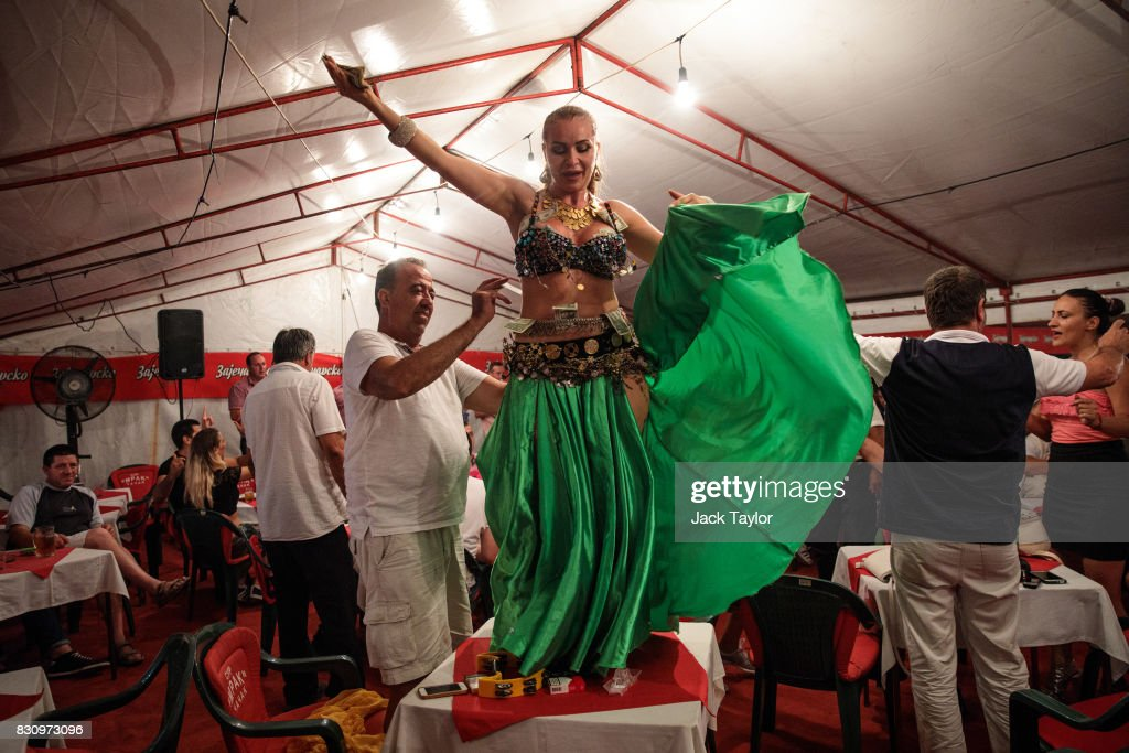A man tips a dancer as she performs on a table in a restaurant during the Guca Trumpet Festival on August 10, 2017 in Guca, Serbia. Thousands of revellers attend the trumpet festival, held annually since 1961 in the small, central Serbian town of Guca. The free event is a celebration of Balkan music with dozens of orchestras and solo trumpeters taking part in the festival's main competition. During the festival wild street parties take place throughout the night as brass bands parade and play for tips to the thousands of visitors in the town's restaurants, bars and pop-up tents.