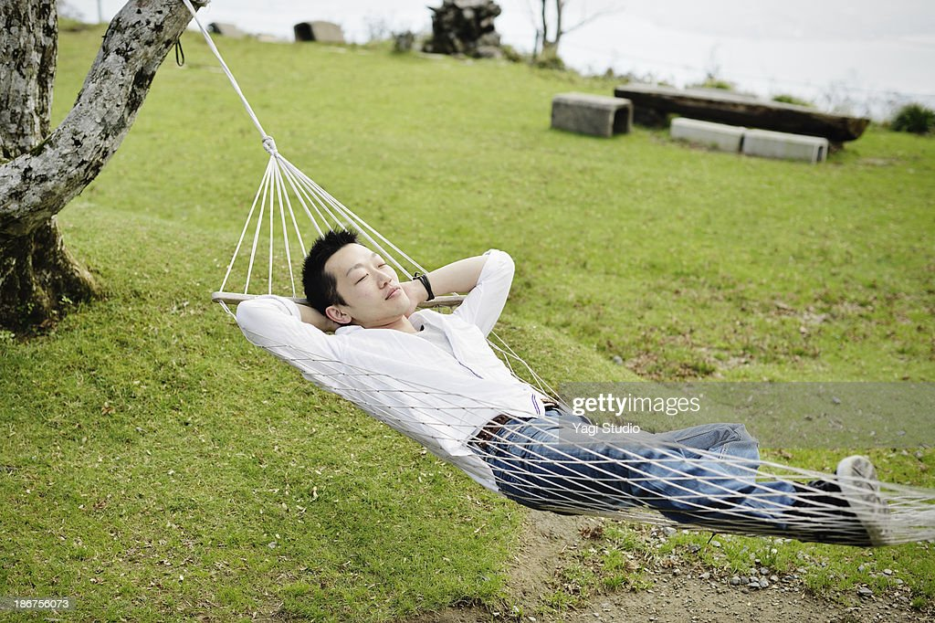 Man to relax in a hammock : ストックフォト