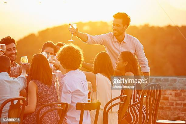 Man toasting wineglass with friends at party
