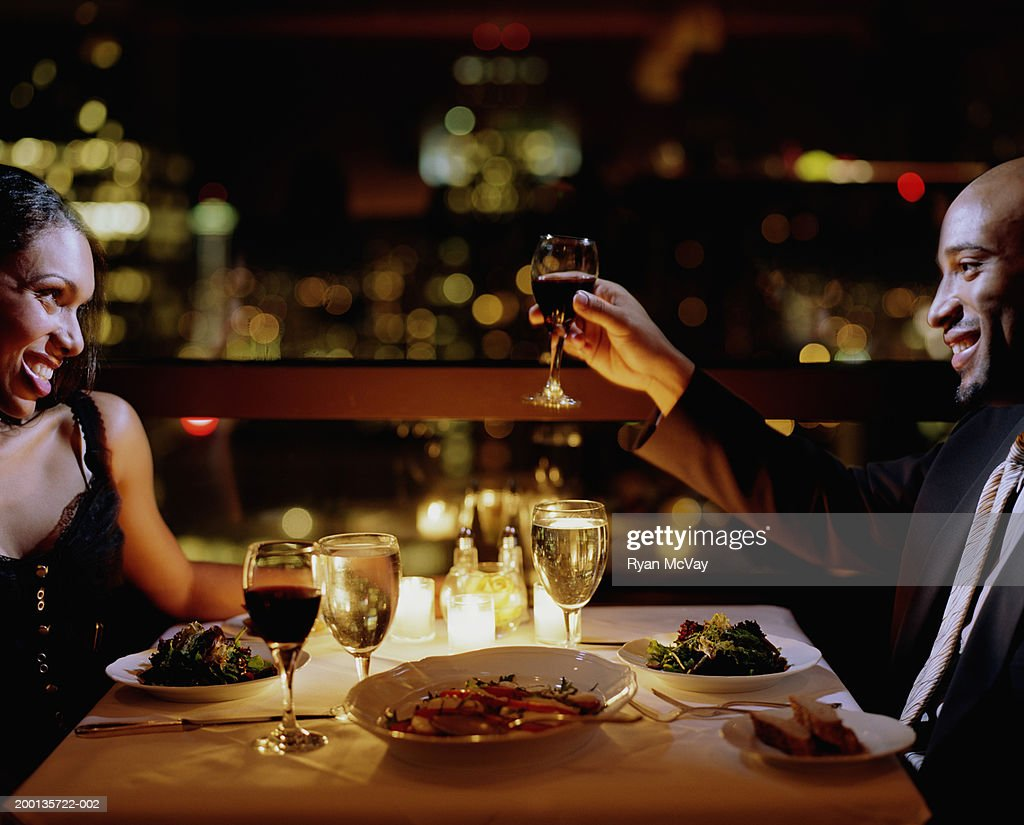 Man toasting woman at restaurant table, side view : Stock Photo