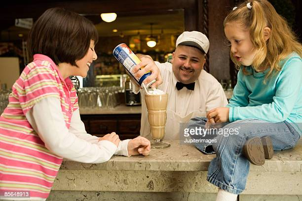 Man topping milkshake with whipped cream