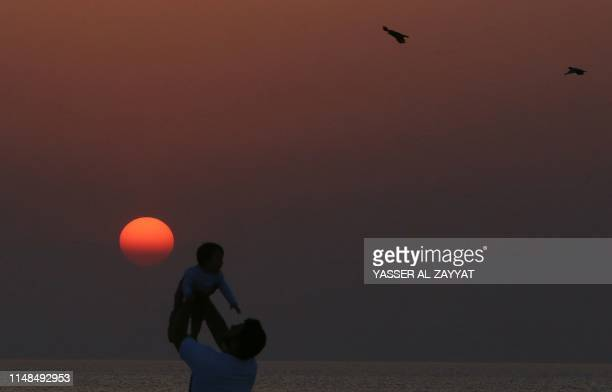 A man tosses a baby against the red sunrise as birds fly past on the beach in Kuwait City on the last day of the Eid alFitr's long weekend marking...
