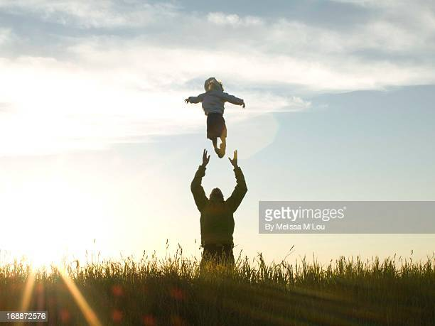 A man tosses a small boy in the air