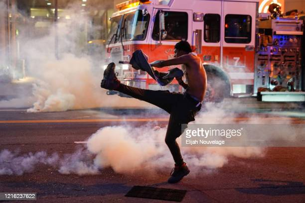 A man tosses back a tear gas canister during a protest on May 29 2020 in Atlanta Georgia Demonstrations are being held across the US after George...