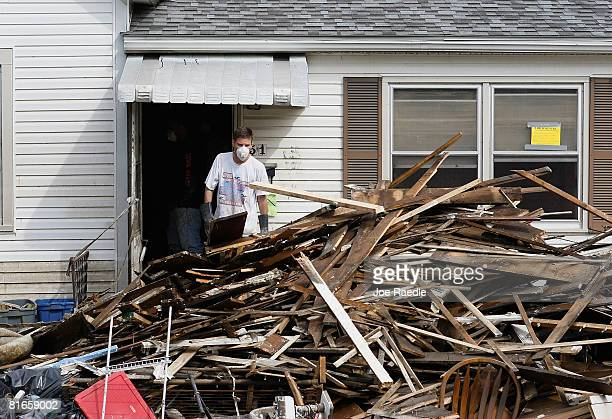 Man tosses wood onto a pile as they gut a home after the Iowa River inundated the house with flood waters June 21, 2008 in Cedar Rapids, Iowa. The...