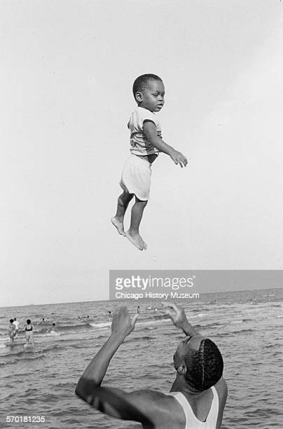 Man tossing a child into the air at 57th Street Beach Chicago Illinois 1988