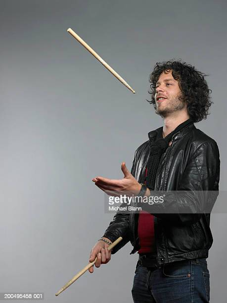 Man tossing and catching drumsticks