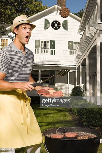 a man tossing barbecue burgers - funny bbq stock pictures, royalty-free photos & images