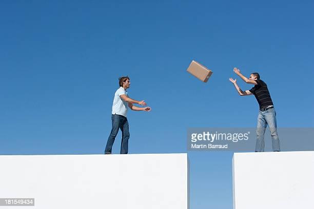 Mann Herumwerfen Pappkarton zu Mann über gap im Freien