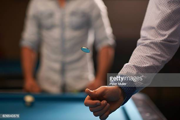 man tossing coin at pool table - flipping a coin stock pictures, royalty-free photos & images