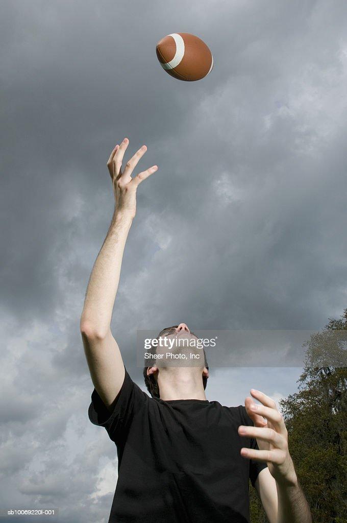 Man tossing football in air : Stockfoto