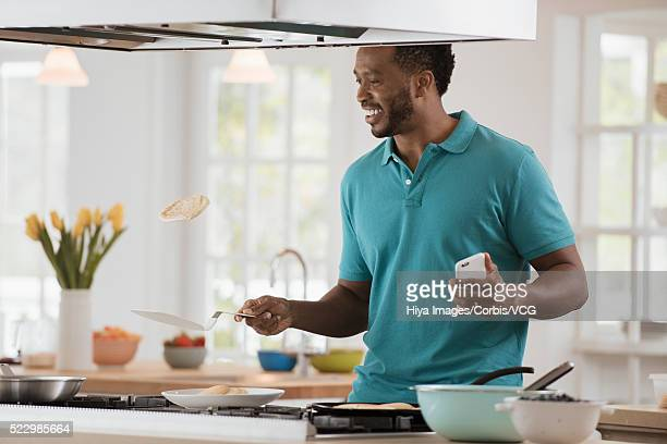 Man tossing pancake in kitchen