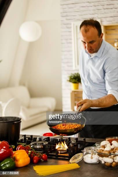 Man tossing pasta in frying pan