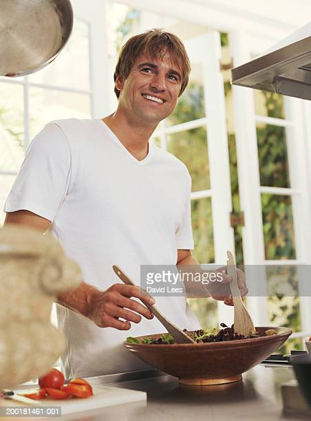 Man tossing salad in bowl, smiling