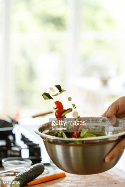 Man tossing vegetable salad