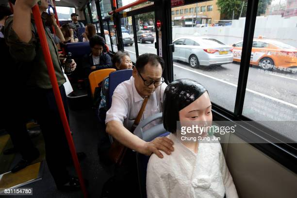A man touches a comfort woman statue in a bus ahead of the 72nd Independence Day on August 14 2017 in Seoul South Korea The statue was originally...