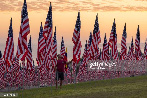 Man touches a flag during the 14th annual Waves of Flags on the eve of the 20th anniversary of the September 11 terror attacks in Alumni Park at...