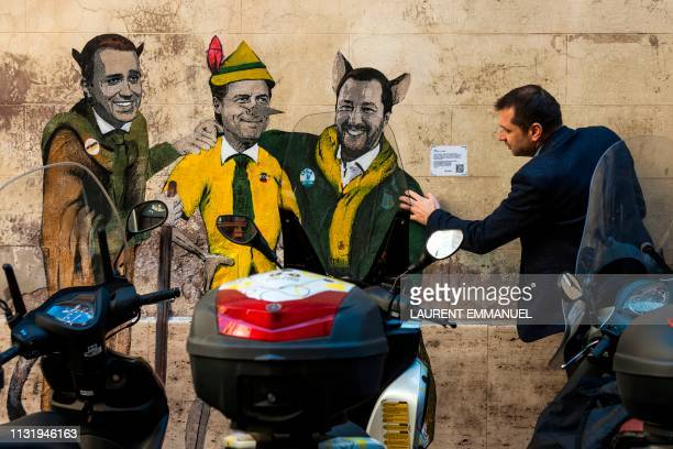 A man touches a mural by Italian street artist TvBoy entitled The cat and the fox Il gatto e la volpe showing Italys Labor and Industry Minister and...