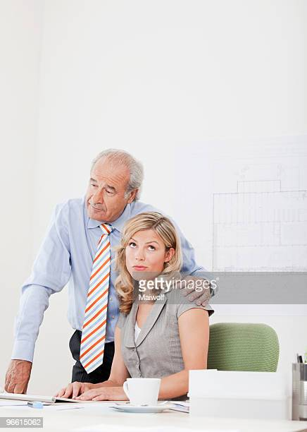 Man touches annoyed co-worker