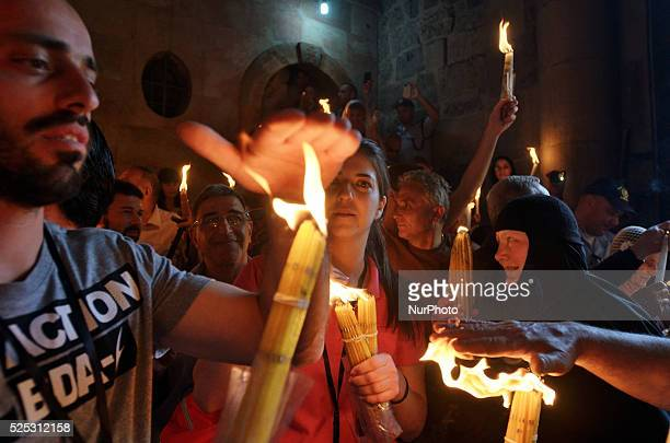 Man touches fire during ceremony of Holy Fire in Holy Sepulcher Church because Christians believe that it didn't burn Jerusalem Israel