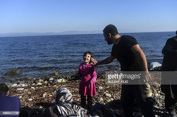 A man touches his daughter's face after they arrived along with other migrants and refugees on the Greek island of Lesbos by crossing the Aegean Sea...