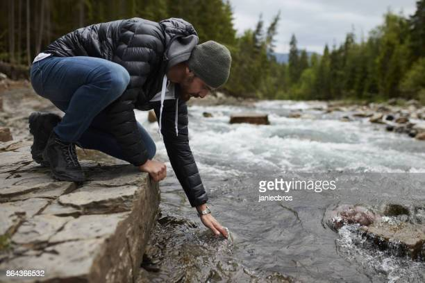man touches surface of mountain river - wilderness stock photos and pictures