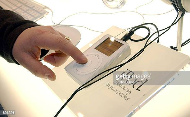 A man touches the Apple iPod mp3 music player on display during the Macworld Conference and Convention January 8 2002 at the Moscone Center in San...