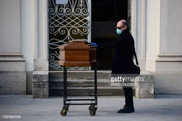 Man touches the coffin of his mother during a funeral service in the closed cemetery of Seriate, near Bergamo, Lombardy, on March 20, 2020 during the...
