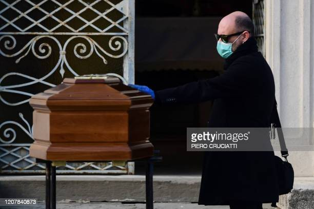 A man touches the coffin of his mother during a funeral service in the closed cemetery of Seriate near Bergamo Lombardy on March 20 2020 during the...