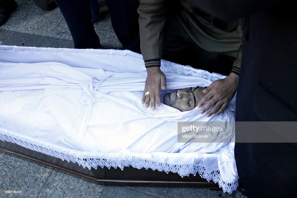 A man touches the face of a body as members of an Athen's Pakistani community gather near the coffin of a 27-year-old Pakistani migrant who was a victim of an alleged racism-fuelled crime on January 19, 2013 in Athens, Greece. Hundreds of Greeks and other nationals marched peacefully against racism on January 19. Long standing as a hub for immigration from the Middle East, Africa and Asia, Greece is under pressure with racial issues as the economic crisis warps the burdens of blame in struggling communities.