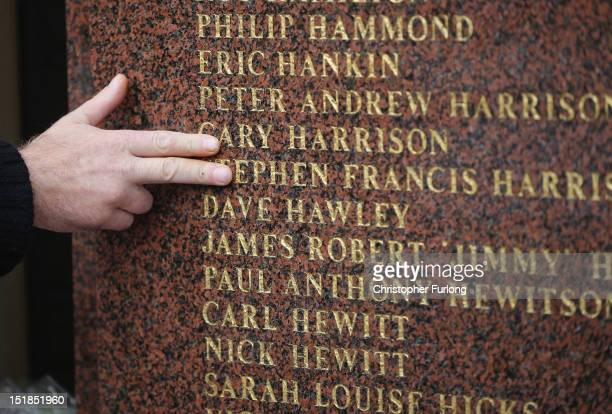 A man touches the names of the victims of the Hillsborough disaster inscribed on the Hillsborough memorial at Anfield stadium after the publication...