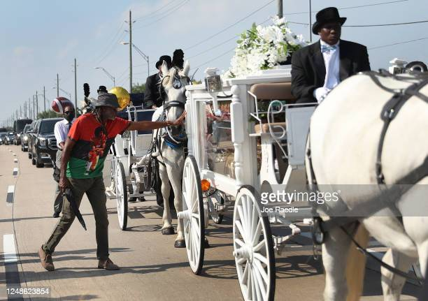 A man touches the side of the horse drawn hearse containing the remains of George Floyd as it makes its way to the Houston Memorial Gardens cemetery...