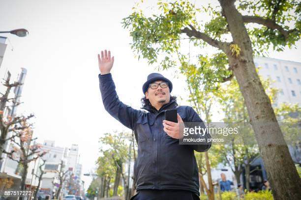 ein mann berühren ein smartphone in einem park - präfektur okayama stock-fotos und bilder