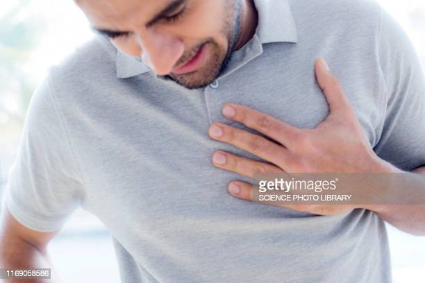 man touching his chest in pain - heart attack stock pictures, royalty-free photos & images