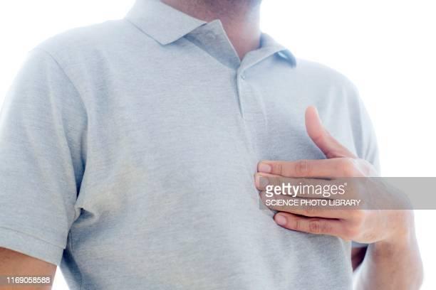 man touching his chest in pain - refluxo gastro esofágico imagens e fotografias de stock