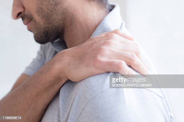 man touching his shoulder in pain - shoulder stock pictures, royalty-free photos & images