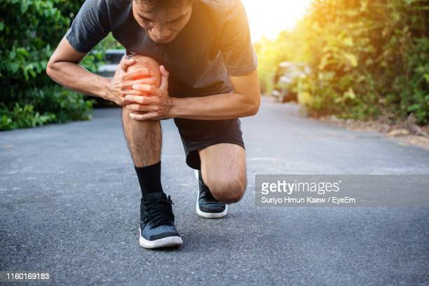 man touching knee in pain on road - human knee stock pictures, royalty-free photos & images