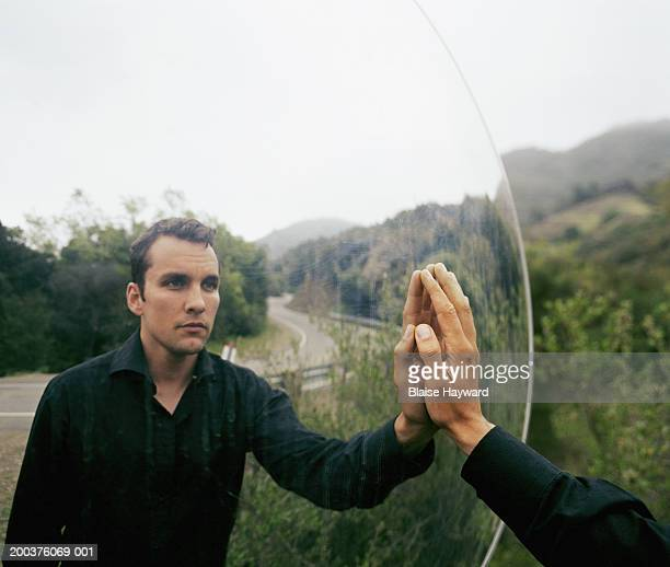 Man touching mirror reflecting hills and road