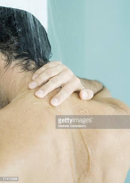 man touching neck in shower - hombre duchandose fotografías e imágenes de stock
