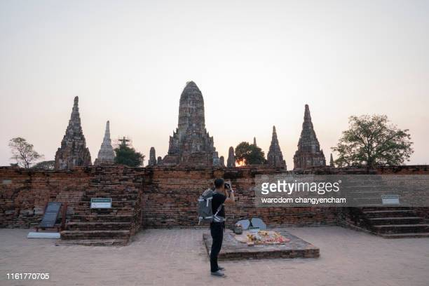 man tourist near the old temple in ayutthaya thailand under sunlight and blue sky. Famous popular touristic place in the world.