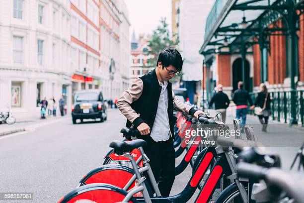 Man tourist renting bicycle on street in London