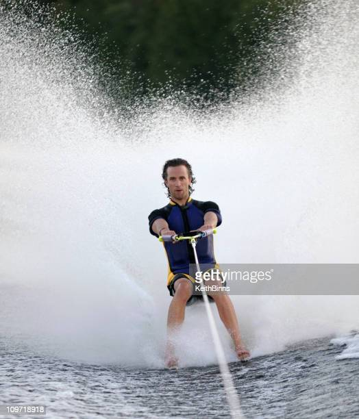 man towed barefoot behind boat - waterskiing stock photos and pictures