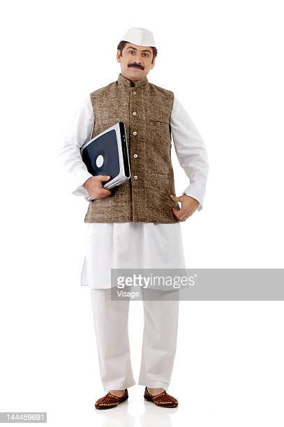 Man traditionally dressed and holding a laptop