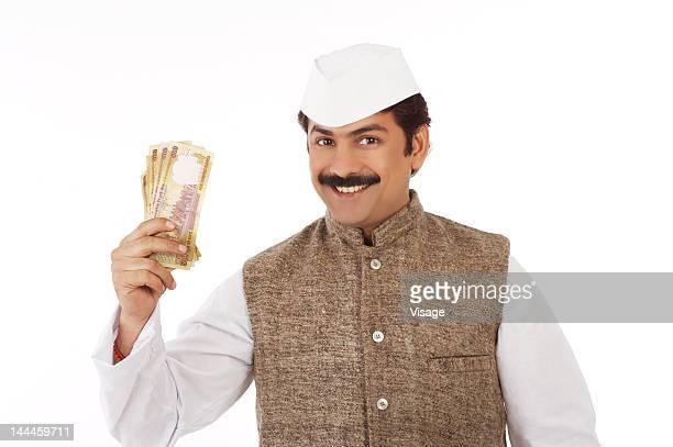 man traditionally dressed holding paper currency - indischer politiker stock-fotos und bilder