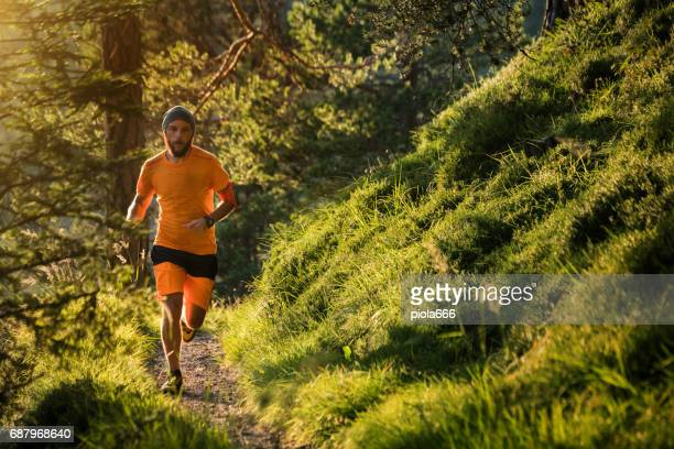 man trail running in the forest up mountain - cross country running stock pictures, royalty-free photos & images