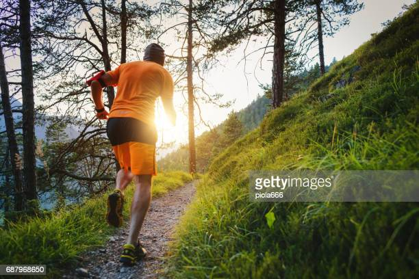 Man trail running in the forest up mountain