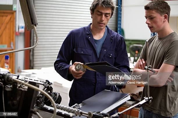 a man training a young man in a printing factory - publisher stock pictures, royalty-free photos & images