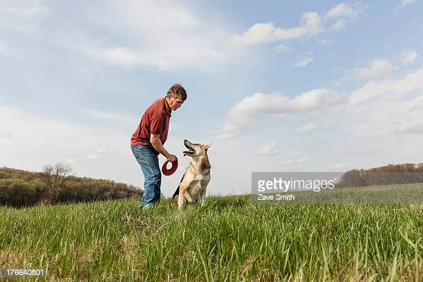 Man training alsatian dog with red frisbee